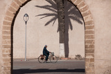 A Local Rides His Bike in the Walled City at Essaouira Photographic Print by Greg Davis
