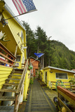 A Bright Yellow Home Adorned with the Alaska State Flag, the American Flag, and Moose Antlers Photographic Print by Jonathan Kingston