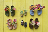 Shoes Nailed to a Bright Yellow Wall Act as Containers for Artificial Flowers Photographic Print by Jonathan Kingston