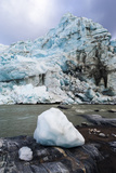 A Block of Ice Carved from a Glacier Resting by a River Photographic Print by Jason Edwards