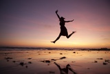 A Woman Jumping on the Beach at Sunset Photographic Print by Macduff Everton