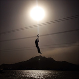 A Man Travels Down a Hipline Above a Lake Outside Beijing Photographic Print by Sean Gallagher