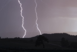 A Cloud-To-Ground Lightning Strike in a Mountainous Valley Photographic Print by Robbie George