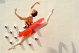 A Ballerina Dancing and Leaping Wearing a Red Dress Photographic Print by Kike Calvo