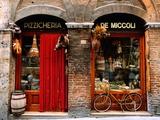 Bicicletta parcheggiata fuori da un negozio di alimentari storico a Siena, Toscana, Italia Poster di John Elk III