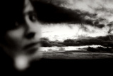 Young Woman Out of Focus in Front of Cloudy Sky Looking into the Camera Photographic Print by Torsten Richter