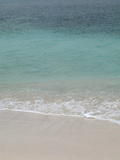 Sea, beach and sand, gentle waves picking up sand particles, Galapagos Islands Photographic Print by Jean Hosking