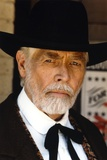 James Coburn Portrait in Black Suit and White Shirt with Black Collar Ribbon and Brimmed Hat Photo by  Movie Star News