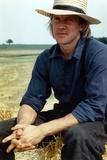 Alexander Godunov sitting on a Hay Stack wearing Blue Long Sleeves and a Hat Photo by  Movie Star News