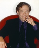 George Segal smiling While Siting on Red Couch in Black Suit and Necktie Photo by  Movie Star News