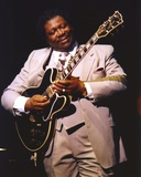 Movie Star News - BB King Performing on Stage using Black Les Paul in Grey Suit with White Cuffs and Collar Shirt Photo