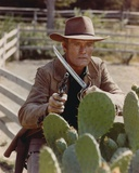 Chuck Connors Holding Weapon in Brown Coat Photo by  Movie Star News