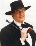 Hugh O'Brien wearing a Black Suit and Hat with Pistol Photo by  Movie Star News