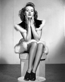 Betty Grable Seated on a Box with Hands on the Chin in Black Pointed Short Sleeve Dress with White  Photo by  Movie Star News