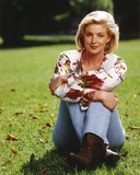 Tracy Needham sitting on the Grass in Floral Blouse Photo by  Movie Star News