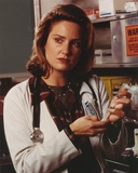 Sherry Stringfield Portrait in Medical Uniform and Brown Collar Shirt with Hands Holding a Syringe Photo by  Movie Star News
