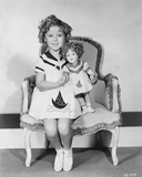 Shirley Temple sitting on Chair with a Doll in White Dress Photo by  Movie Star News