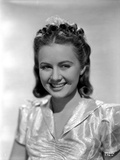 Ann Gillis smiling and wearing a Glossy Blouse Portrait Photo by  Movie Star News