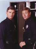 Adam-12 Posed in Police Uniform Looking at the Camera Near the Shelf in a Portrait Photo by  Movie Star News