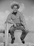 Alan Ladd sitting on a Fence in Cowboy Outfit Photo by  Movie Star News