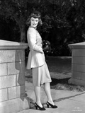 Alexis Smith Leaning on a Stone Fence wearing a Suit Photo af Movie Star News