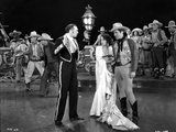 Bebe Daniels standing in White Long Dress while Two Men in Cowboy Outfit and Matador Outfit standin Photo by  Movie Star News