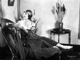 Betty Blythe sitting on the Reclining Bed in Strap Dress and Black Sheer Mufflers with Silk Headban Photo by  Movie Star News