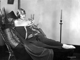 Betty Blythe Lying on the Black Reclining Bed in Black Strapless Sheer Sleeve Velvet Dress and Cott Photo by  Movie Star News