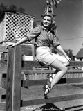 Claire Trevor sitting on Wood Fence with Heels Photo by  Movie Star News