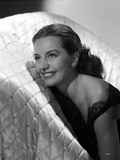 Cyd Charisse smiling in a White Couch wearing Black Sleeveless Dress and an Earrings Photo by  Movie Star News