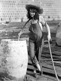 Fay Wray Filling Up Drum with Water in Jumper Photo by  Movie Star News