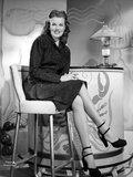 Janis Paige sitting on a White Chair in Black V-Neck Long Sleeve Linen Shirt and Black High Heel Sh Photo by  Movie Star News
