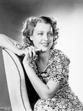 Jeanette MacDonald sitting on a White Chair in Black Short Sleeve Floral Dress with Hands Together  Photo by  Movie Star News