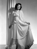 Jane Withers Posed in White Silk Keyhole-Neck Long Sleeve Dress with Left Hand Holding Skirt Up Photo by  Movie Star News