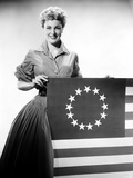 Jan Sterling Posed in Velvet Long Sleeve Dress and Accordion Pleated Skirt while Holding a Flag Photo by  Movie Star News