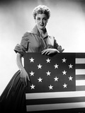 Jan Sterling Posed in Velvet Shirt and Pleated Skirt with Rolled Up Sleeves while Holding a Flag Photo by  Movie Star News