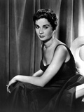 Jean Simmons Seated on a Couch in Black Velvet Strap Dress with Left Arm on the Lap Photo by  Movie Star News