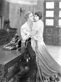 John Barrymore sitting on the Table while Holding on a Woman Photo by  Movie Star News