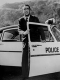 Macdonald Carey standing in Black Suit With Police Car Photo by  Movie Star News