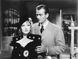 Marlene Dietrich standing in Black Dress with Man, wearing Checkered Suit Photo by  Movie Star News
