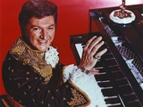 Liberace with Man Playing Piano in Red Background Photo by  Movie Star News