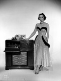 Jane Wyman Posed in White Silk Dress with Gathered Long Skirt with Right Hand on the Radio Box Photo by  Movie Star News