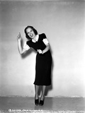 Jane Wyman Posed in Black Velvet Short Sleeve Dress with White Ruffle Collar and Sleeves while Hand Photo by  Movie Star News