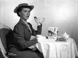 Phyllis Kirk Seated while Holding Cookie in Black Formal Dress with Hat Photo by  Movie Star News