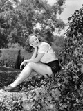 Vera Zorina sitting on vine covered rock, with her head leaned into her head, smiling away from the Photo by  Movie Star News
