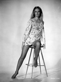 Veronica Carlson posed sitting on stool with one foot resting on the foot rest, wearing floral dres Photo by  Movie Star News