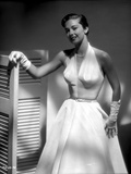 Vera Miles photographed wearing an elegant belted,  white organza, deep v-neck, sleevless gown and  Photo by  Movie Star News