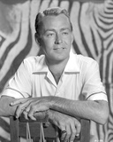 Alan Ladd smiling and posed on the Chair in Black and White Portrait Photo by  Movie Star News