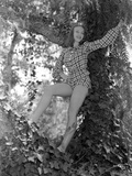 Vera Zorina smiling broadly, standing in tree, wearing a checkered, long-sleeve romper. Photo by  Movie Star News