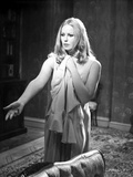 Veronica Carlson standing with arm raised and hand out, clutching a jacket to her chest Photo by  Movie Star News